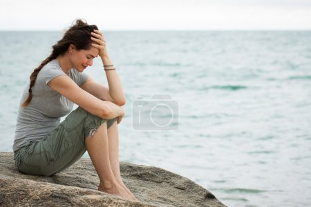 Photo for Upset and depressed woman sitting by the ocean crying with her head in her hand. - Royalty Free Image