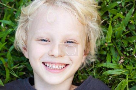 Souriant jeune garçon allongé dans l'herbe souriant