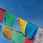 Buddhist tibetan prayer flags flying with blue sky...
