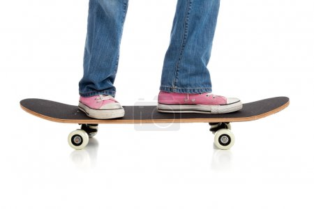 A girls legs in jean and pink sneakers riding a skateboard on a white background