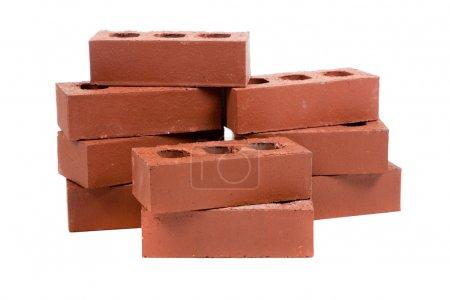 Photo pour Une pile de briques rouges sur un fond blanc avec une truelle pointue - image libre de droit