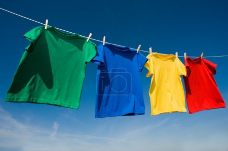Photo for A group of primary colored t-shirts ona clothesline in front of blue sky - Royalty Free Image