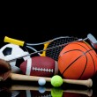 A group of sports equipment on black background in...