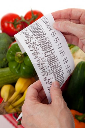 Photo for A grecery receipt over a bag of vegetables - Royalty Free Image