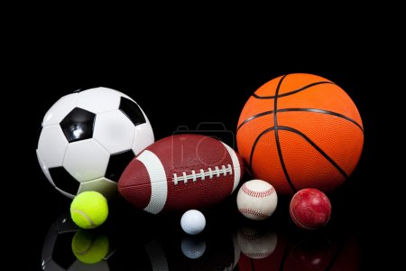 Photo for Assorted sports balls including a basketball, american football, soccer ball, tennis ball, baseball, golf ball and cricket ball on a black background - Royalty Free Image