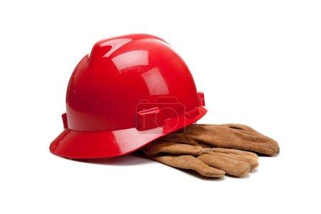 Photo pour Un casque rouge et des gants de travail en cuir sur fond blanc - image libre de droit