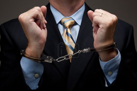 Photo for White collar criminal in a business suit and handcuffs - Royalty Free Image