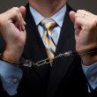 White collar criminal in a business suit and handc...