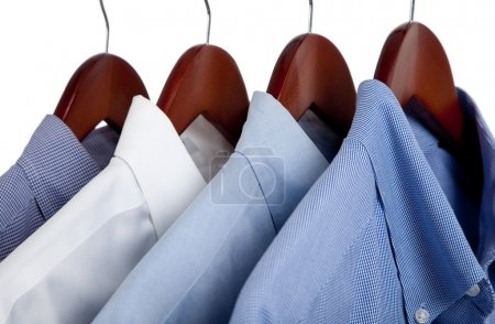 Photo for Assorted blue dress hanging on wooden hangers - Royalty Free Image