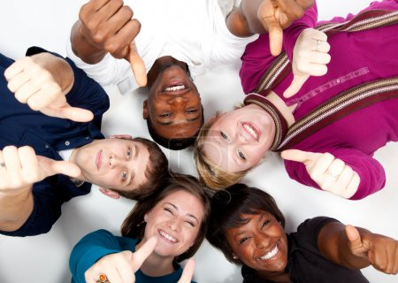Photo for Faces of smiling multi-racial college students with their thumbs up - Royalty Free Image