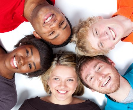 Photo for Close-up of faces of Multi-racial college students lying on the ground - Royalty Free Image