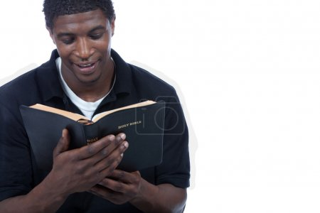 Photo for A young black man reading the Holy Bible on a white background - Royalty Free Image