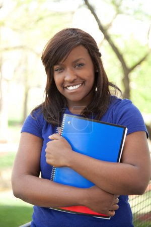 Photo for A pretty female African-American college or universtiy student holding books, outdoors - Royalty Free Image