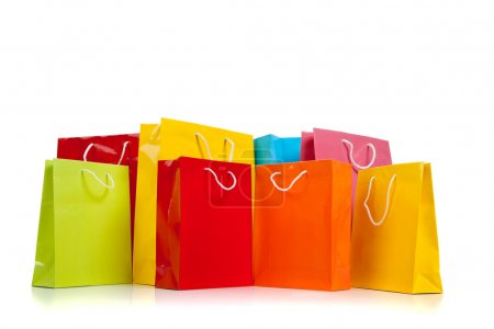 Photo for Assorted colored shopping bags including red, yellow, lime green, orange, pink and blue on a white background - Royalty Free Image