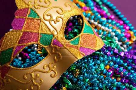 Photo for A background made up of a gold mardi gras mask and blue, purple, green and pink beads - Royalty Free Image