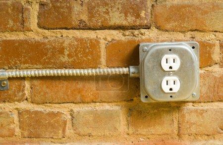 Photo pour Une prise de courant industrielle sur un mur de briques avec espace copie - image libre de droit