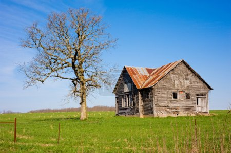 An old dilapidated farm house or store next to a d...