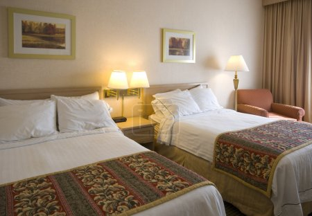 Photo for A hotel room with two beds, lamps, pictues chairs and pillows - Royalty Free Image