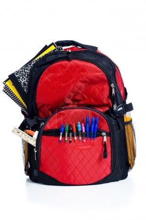 Photo pour Une retour de l'école rouge pack ou sac à livres débordant d'école fournit notamment, cahiers, stylos, crayons, règles et colle - image libre de droit