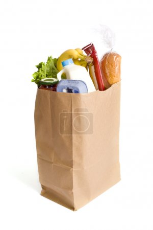 Photo for A brown kraft bag full of groceries including, milk, eggs, bread etc - Royalty Free Image