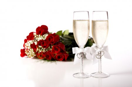 Photo for A bouquet of red roses and tow champange flutes or toasting glasses with champagne on a white background - Royalty Free Image