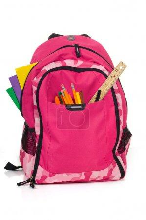 Photo pour Fournitures de bureau rose sac à dos avec l'école sur fond blanc avec dossiers, stylos, une règle et colle - image libre de droit