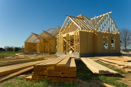 Photo for New home under construction with wood, trusses and supplies against blue sky - Royalty Free Image