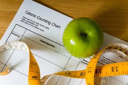 Photo for Calorie counting chart, green apple and tape measure, items for a diet - Royalty Free Image