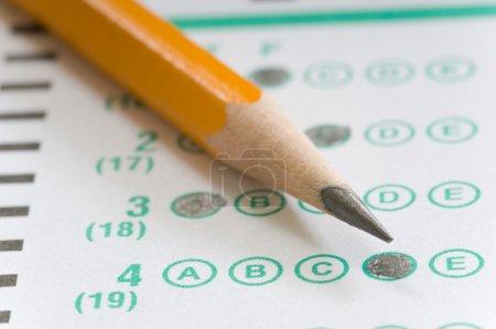 Photo pour Crayon jaune sur la feuille de réponse informatisée du test à choix multiples - l'accent est mis sur la lettre D de la réponse numéro 4 - image libre de droit