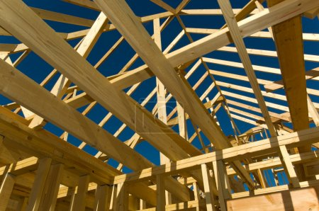 Photo for Housing construction industry with the frame of a house with wood against a blue sky - Royalty Free Image