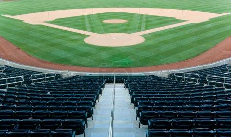 Photo pour Stade de baseball avec des sièges et un terrain de baseball avec l'herbe verte - image libre de droit