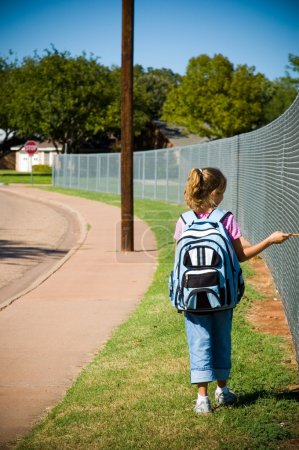 Photo for Young girl walking by school yard on first day of school with backpack and pencil - Royalty Free Image
