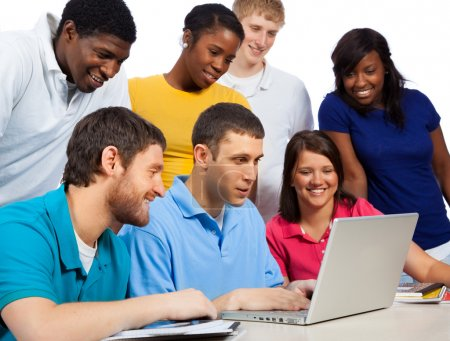 Photo for A group of multi-cultural college students/friends gathered around a computer - Royalty Free Image