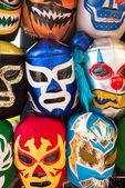 Elrendezése különböző luchador maszkok a háttérben
