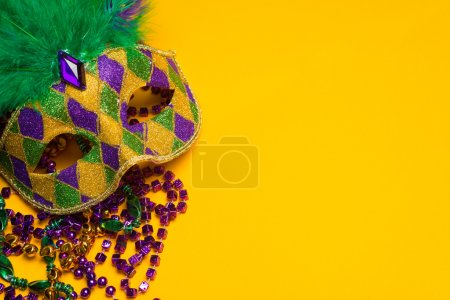Photo for A festive, colorful group of mardi gras or carnivale mask on a yellow background. Venetian masks. - Royalty Free Image