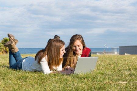 Las niñas con un ordenador portátil
