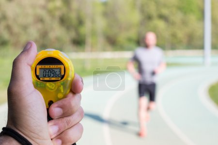 Photo for Coach clocking times in a running track - Royalty Free Image