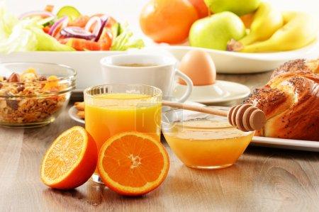 Photo for Breakfast including coffee, bread, honey, orange juice, muesli and fruits - Royalty Free Image