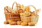 Chleba a rohlíky v proutěném koši izolované na bílém