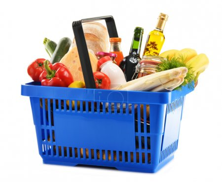 Photo for Plastic shopping basket with variety of grocery products isolated on white - Royalty Free Image