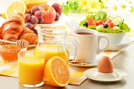 Breakfast with coffee, orange juice, croissant, egg, vegetables