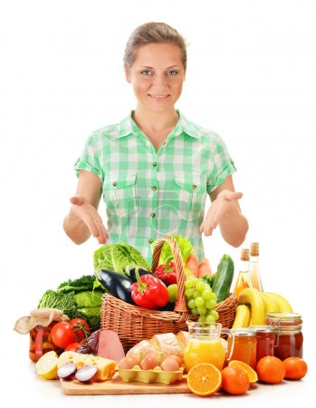 Young woman with variety of grocery products isolated on white