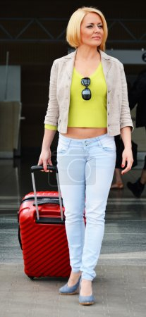 Young woman with luggage at the airport. Traveling tourist