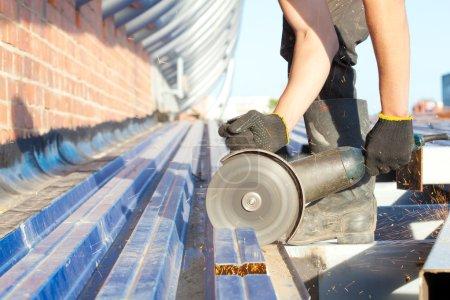 Construction worker sawing steel sheet