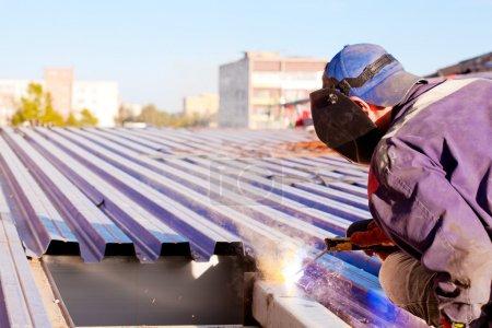Photo pour Soudeur en uniforme et masque pendant les travaux de toiture au moyen d'une machine à souder onduleur - image libre de droit
