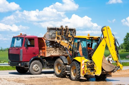 Photo for Wheel loader Excavator unloading sand into truck body during earthmoving works at construction site - Royalty Free Image