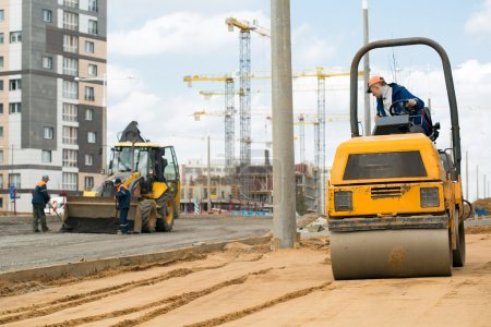 Road roller compacting sand during road works