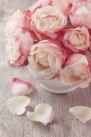Pink roses and petals on wooden desk...