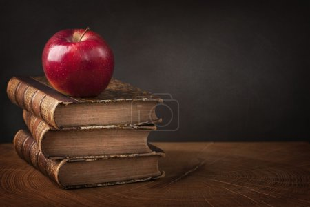 Photo pour Empilement de livres et pomme rouge sur table en bois - image libre de droit