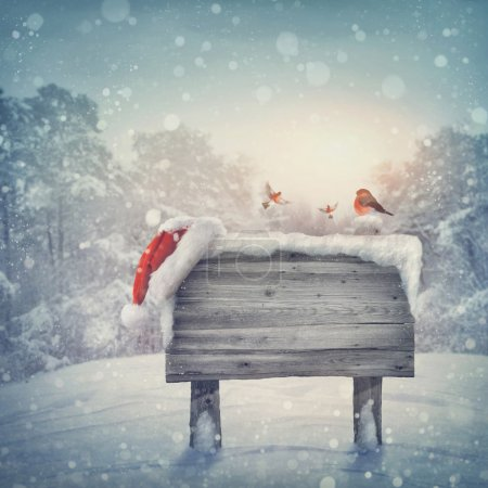 Photo for Wooden sign and santa hat in winter forest - Royalty Free Image